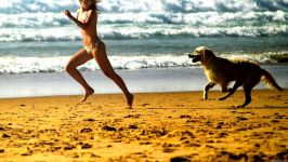 Девушка бежит по пляжу с золотистым ретривером
